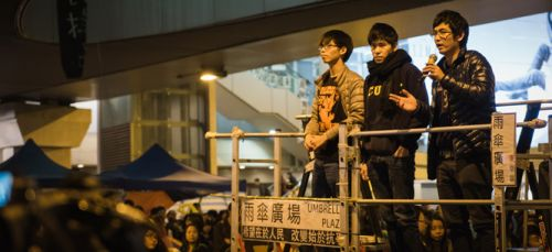 Alex Chow (right) addressing protesters during Hong Kong's Umbrella movement, alongside fellow student leaders Joshua Wong (left) and Lester Shum, December 2014 (Studio Incendo / Flickr)